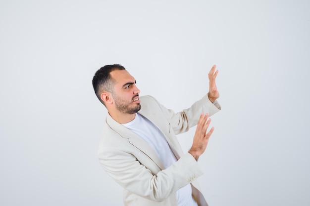 Jovem esticando as mãos, parando algo em camiseta branca, jaqueta e parecendo assustado. vista frontal.
