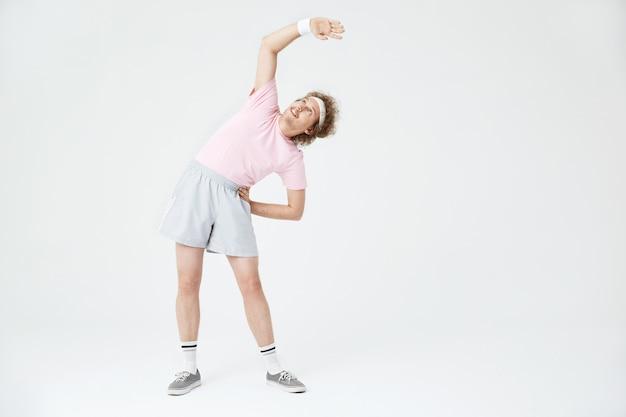 Jovem, esticando os músculos das costas, inclinando-se para a esquerda. estilo antigo