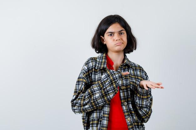 Jovem, esticando uma mão segurando algo e apontando para ele com o dedo indicador em uma camisa xadrez e uma camiseta vermelha e olhando séria. vista frontal.