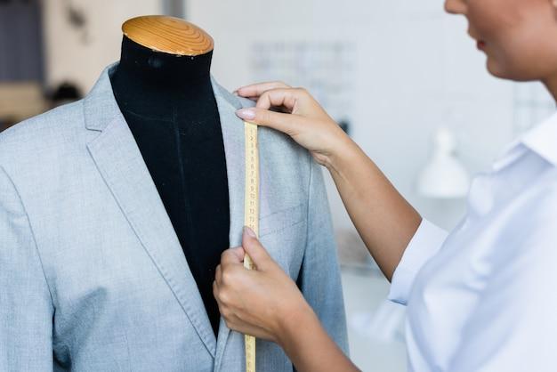 Jovem estilista contemporâneo com fita amarela medindo o comprimento da gola da jaqueta enquanto fica de pé ao lado do manequim na oficina