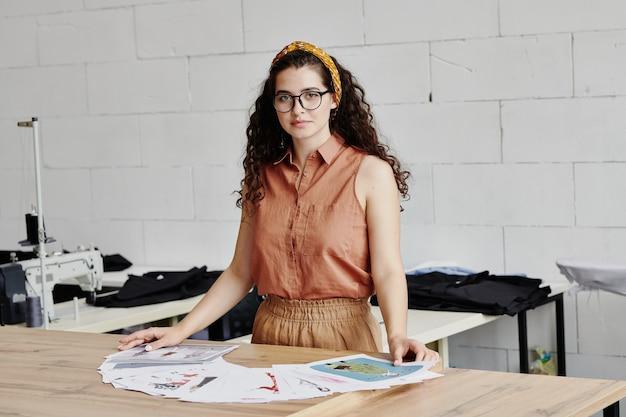 Jovem estilista de moda feminina com cabelo escuro comprido ondulado em pé ao lado da mesa com desenhos e escolhendo alguns para a nova coleção