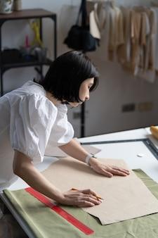 Jovem estilista em estúdio trabalha em padrões. a costureira prepara rascunhos e tecidos para esboçar
