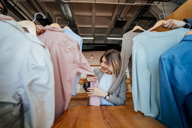 Jovem estilista olhando através de um conjunto de camisas para fotografar moda