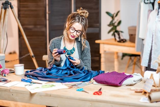 Jovem estilista trabalhando com tecido azul, sentada no lindo escritório com diferentes ferramentas de alfaiataria na mesa