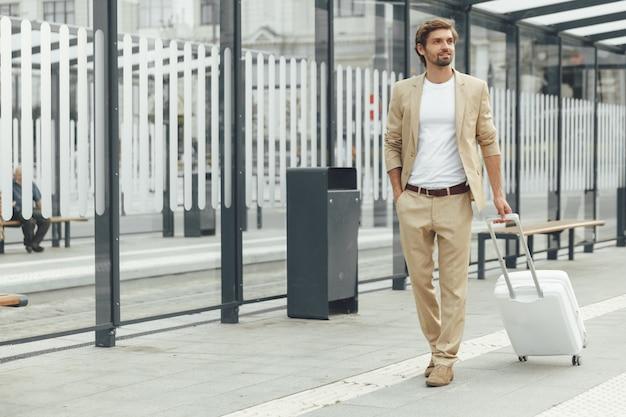 Jovem estiloso com barba segurando uma mala branca enquanto está no ponto de ônibus