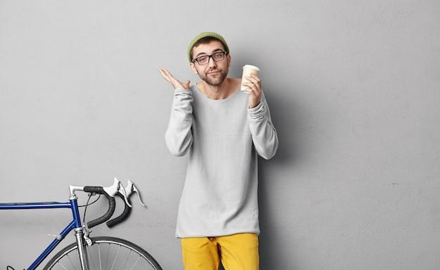 Jovem estiloso em pé perto de uma bicicleta