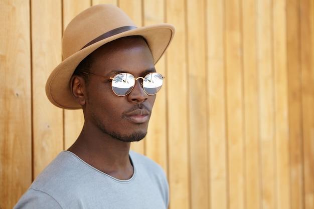 Jovem estiloso usando chapéu e óculos escuros