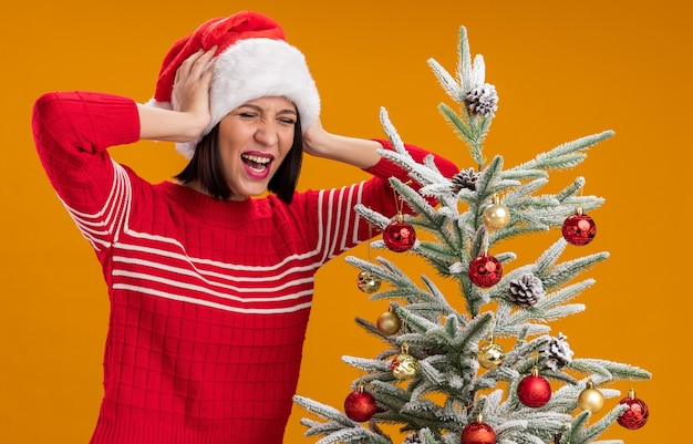 Jovem estressada com chapéu de papai noel em pé perto da árvore de natal decorada, mantendo as mãos na cabeça, gritando com os olhos fechados, isolado em um fundo laranja