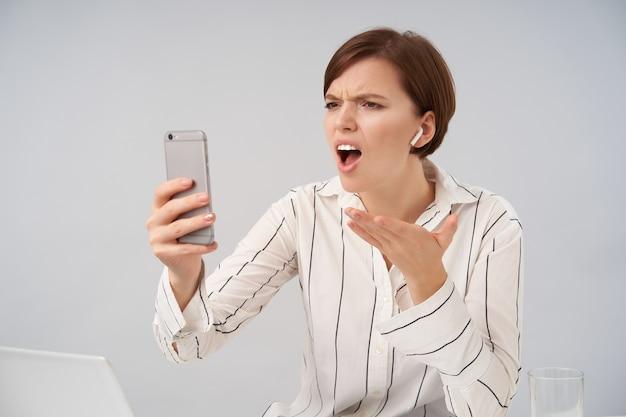Jovem estressada de cabelos curtos de olhos castanhos com maquiagem natural levantando emocionalmente a palma da mão enquanto conversa por vídeo desagradável com seu smartphone, sentada no branco