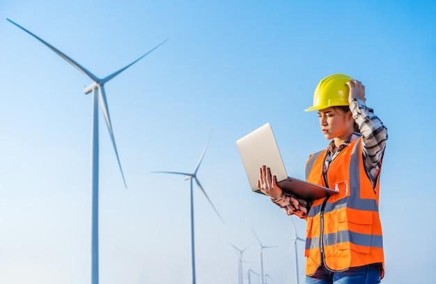 Jovem estressada, engenheira, tendo problemas para trabalhar com um laptop contra uma fazenda de turbinas eólicas