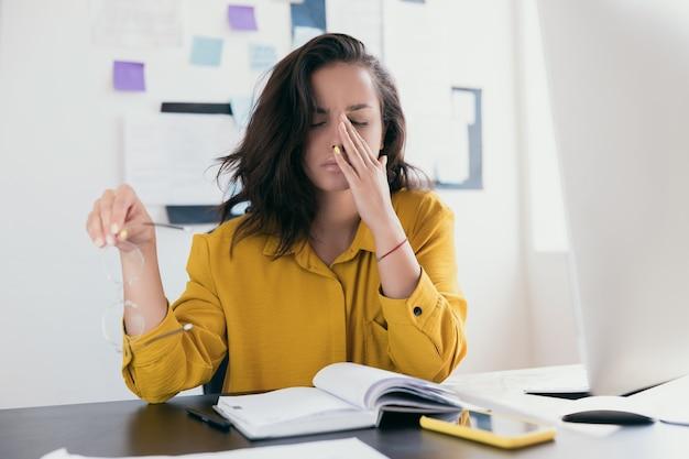 Jovem estressada no escritório, segurando os óculos