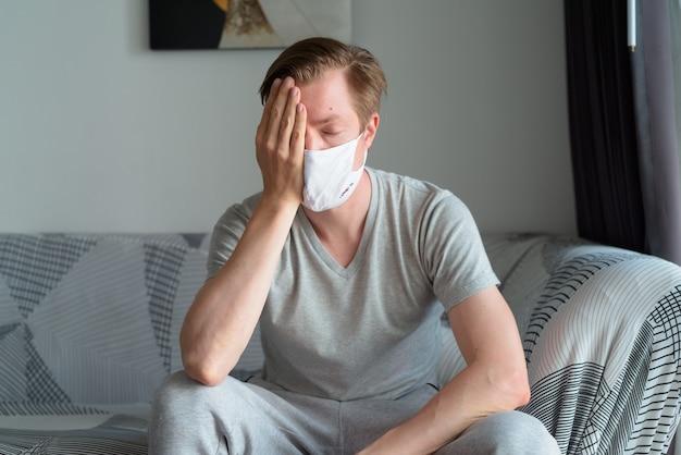 Jovem estressado com máscara recebendo más notícias em casa em quarentena