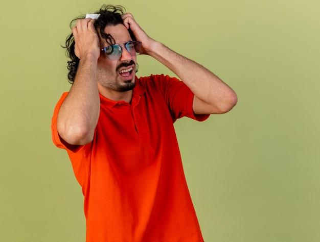 Jovem estressado e doente, usando óculos, segurando um guardanapo, colocando as mãos na cabeça com os olhos fechados, isolado na parede verde oliva com espaço de cópia