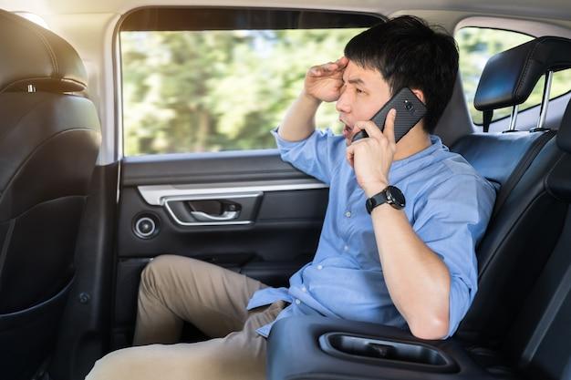 Jovem estressado falando sobre o problema em um telefone celular enquanto está sentado no banco de trás do carro