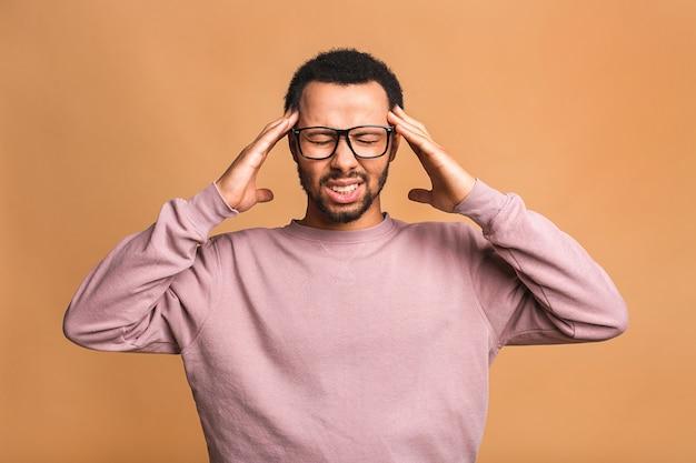 Jovem estressado sente dor com o conceito de dor de cabeça forte e terrível, cara chateado e cansado massageando têmporas sofrendo de enxaqueca isolada sobre bege