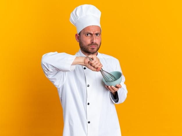 Jovem estrito cozinheiro caucasiano com uniforme de chef e boné batendo ovo na tigela