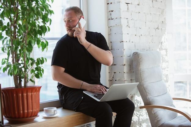 Jovem estudando em casa durante cursos online para análise, financistas, economistas. obter profissão enquanto isolado, quarentena contra a propagação do coronavírus. usando laptop, smartphone, dispositivos.