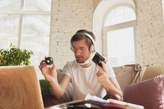 Jovem estudando em casa durante cursos online para assistente de fotógrafo