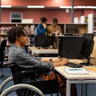 Jovem estudando na biblioteca da universidade