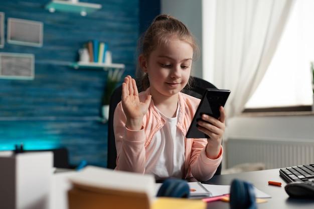 Jovem estudante acenando para uma câmera de videochamada no smartphone