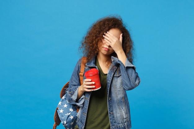 Jovem estudante adolescente afro-americana com roupas jeans, mochila segurando copo de papel isolado na parede azul
