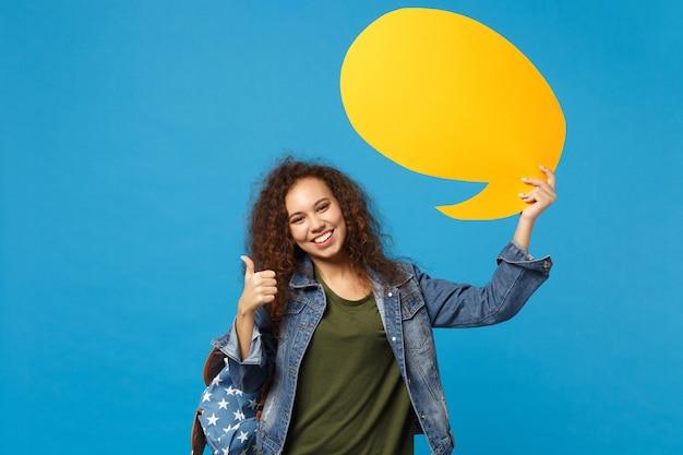 Jovem estudante adolescente afro-americana com roupas jeans, mochila segurando, digamos, nuvem isolada na parede azul