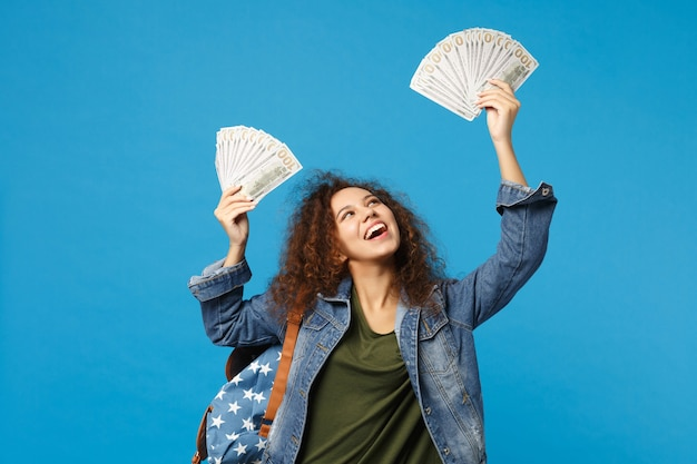 Jovem estudante adolescente afro-americana com roupas jeans, mochila segurando dinheiro isolado na parede azul