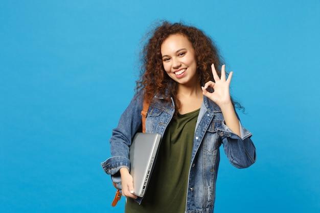 Jovem estudante adolescente afro-americana com roupas jeans, mochila segurando pc isolado na parede azul