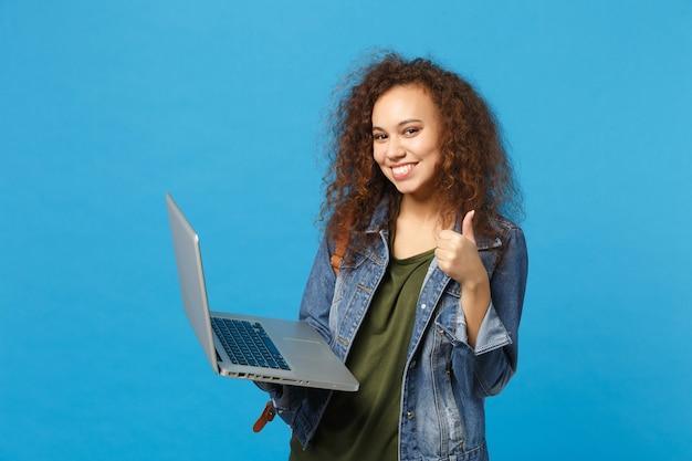 Jovem estudante adolescente afro-americana com roupas jeans, mochila trabalhando no pc isolada na parede azul Foto gratuita