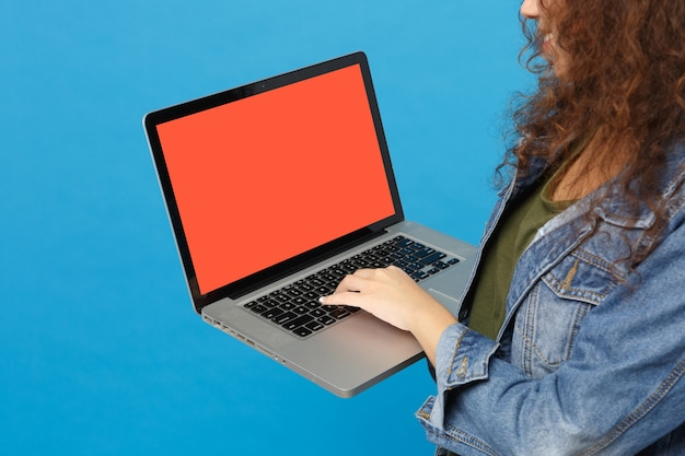 Jovem estudante adolescente afro-americana com roupas jeans, mochila trabalhando no pc isolada na parede azul