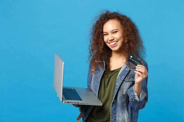 Jovem estudante adolescente afro-americana com roupas jeans, mochila trabalhando no pc, segurando o cartão do banco isolado na parede azul
