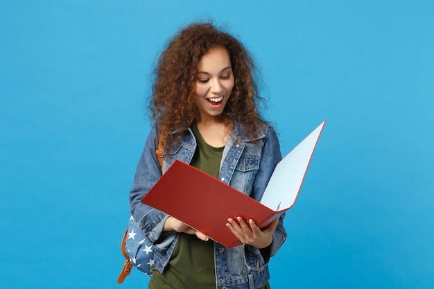 Jovem estudante adolescente afro-americana em mochila jeans segurando pasta isolada na parede azul