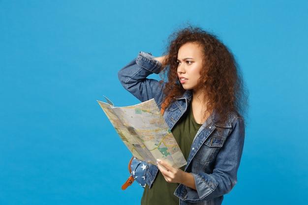 Jovem estudante adolescente afro-americana em roupas jeans, mochila segura mapa isolado na parede azul