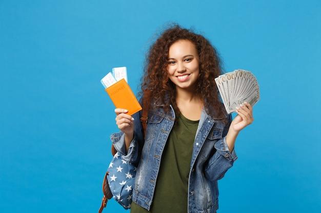Jovem estudante adolescente afro-americana em roupas jeans, mochila segura passagem isolada na parede azul