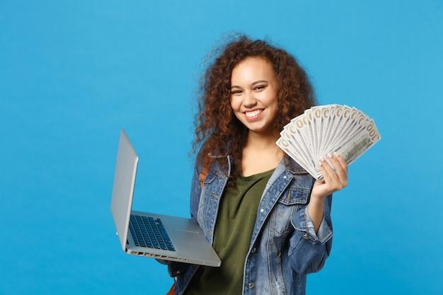 Jovem estudante adolescente afro-americana em roupas jeans, mochila segura pc, fã de dinheiro isolado na parede azul