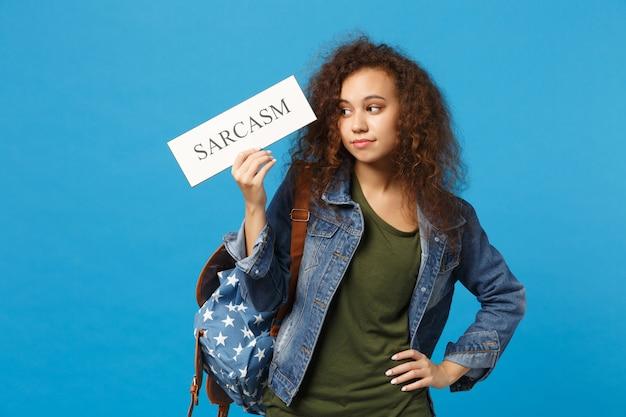 Jovem estudante adolescente afro-americana em roupas jeans, mochila segura placa isolada na parede azul