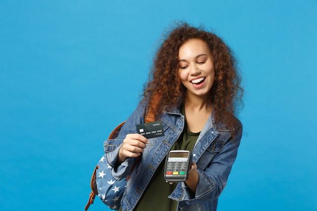Jovem estudante adolescente afro-americana em roupas jeans, mochila segurando cartão de crédito isolado na parede azul