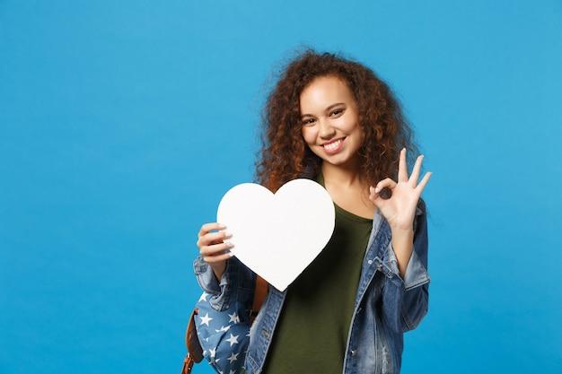 Jovem estudante adolescente afro-americana em roupas jeans, mochila segurando coração isolado na parede azul