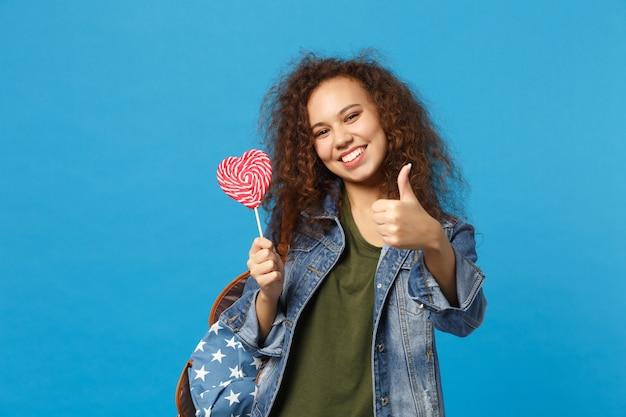 Jovem estudante adolescente afro-americana em roupas jeans, mochila segurando doces isolados na parede azul