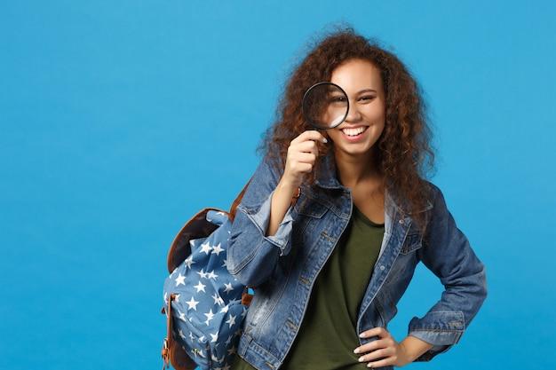 Jovem estudante adolescente afro-americana em roupas jeans, mochila segurando o relógio isolado na parede azul