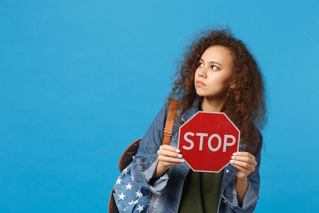 Jovem estudante adolescente afro-americana em roupas jeans, mochila segurando parada isolada na parede azul