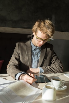 Jovem estudante adolescente masculino moderno trabalha atentamente com tablet pc e livros em dia ensolarado em restaurante acolhedor
