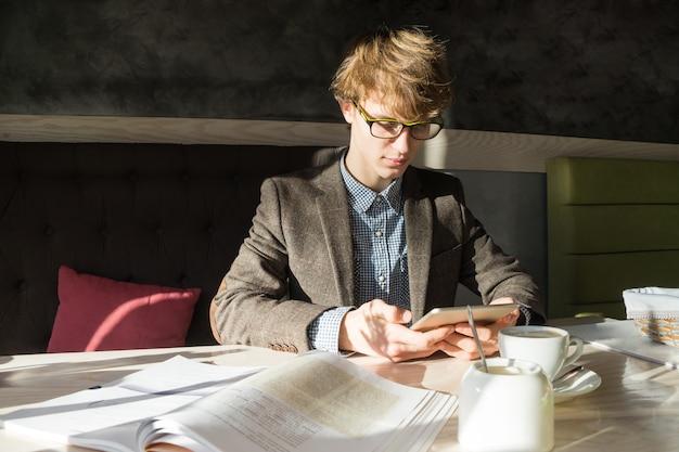 Jovem estudante adolescente masculino moderno trabalha com tablet pc e livros em dia ensolarado em restaurante acolhedor