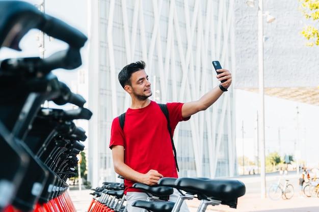 Jovem estudante adulto tirando uma selfie com seu celular em uma cabine de aluguel de bicicletas Foto Premium