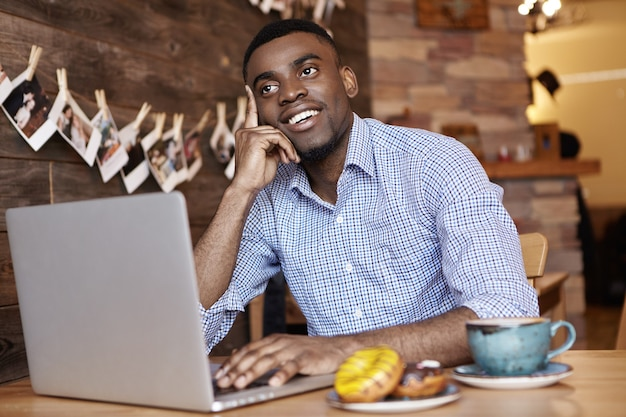Jovem estudante africana alegre com uma camisa formal a pensar