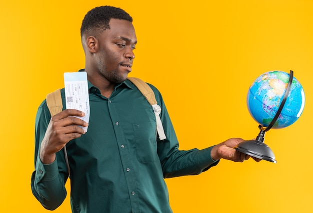Jovem estudante afro-americana satisfeita com uma mochila segurando uma passagem aérea e olhando para o globo isolado na parede laranja com espaço de cópia