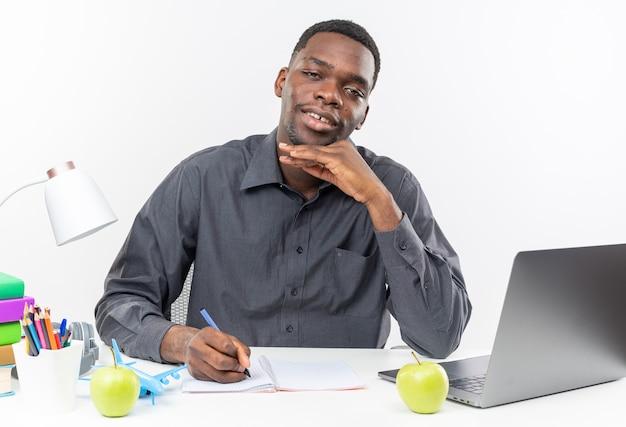 Jovem estudante afro-americana satisfeita, sentada na mesa com as ferramentas da escola, escrevendo no caderno com uma caneta isolada na parede branca