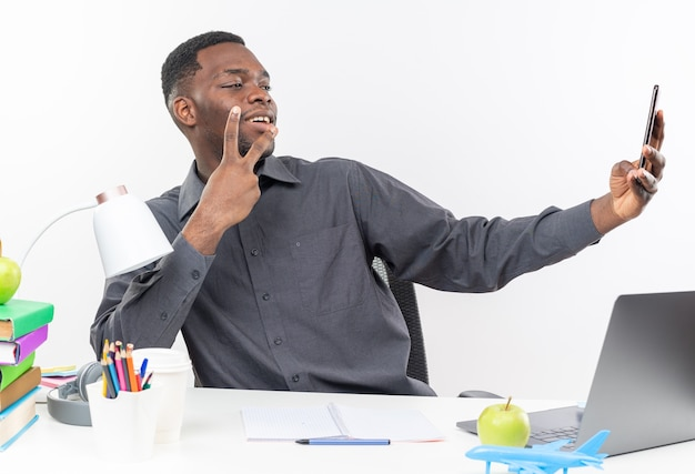 Jovem estudante afro-americana satisfeita, sentada na mesa com as ferramentas da escola, gesticulando no sinal da vitória e tirando uma selfie no telefone