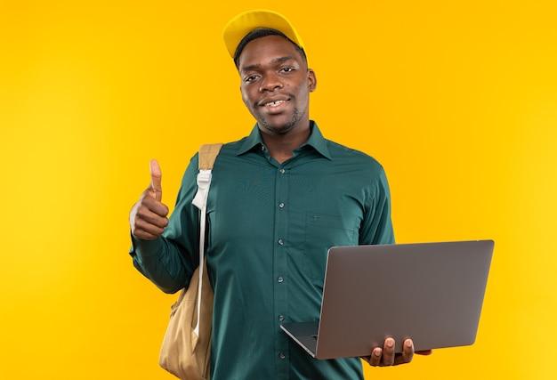 Jovem estudante afro-americana sorridente com boné e mochila segurando um laptop e apontando para cima