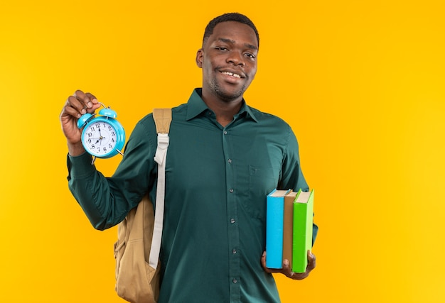 Jovem estudante afro-americana sorridente com uma mochila segurando livros e despertador